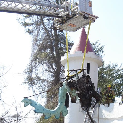 The Howard County Fire Department removes the remains of the Dragon from the Castle parapet